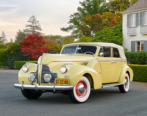 AUT 20 RK0708 01 © Kimball Stock 1940 Buick Phaeton Limited Convertible Yellow 3/4 Front View On Pavement By House