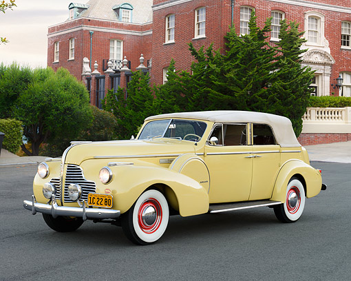 AUT 20 RK0709 01 © Kimball Stock 1940 Buick Phaeton Limited Convertible Yellow 3/4 Front View On Pavement By House