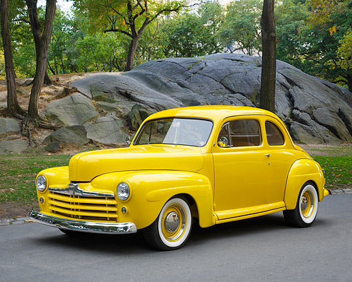 AUT 20 RK0739 01 © Kimball Stock 1947 Ford Coupe Yellow 3/4 Front View By Trees