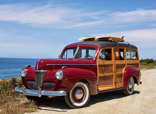 AUT 20 RK0742 01 © Kimball Stock 1941 Ford Woodie Station Wagon With Surf Boards Maroon 3/4 Front View By Ocean