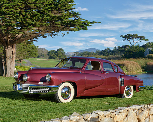 AUT 20 RK0747 01 © Kimball Stock 1948 Tucker 48 Torpedo Maroon 3/4 Front View By Trees And Lake