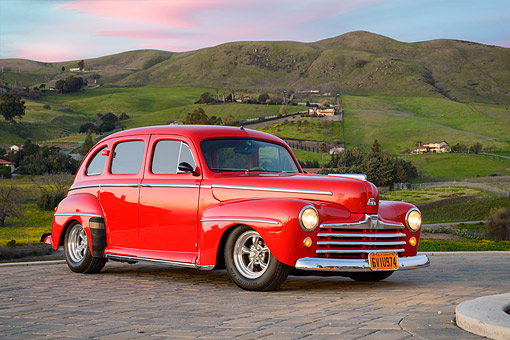 AUT 20 RK0765 01 © Kimball Stock 1947 Ford Super Deluxe Red 3/4 Front View On Cobblestone Road By Grassy Hills