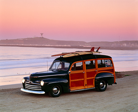 AUT 20 RK0013 01 © Kimball Stock 1946 Ford Woody With Surfboards Dark Green 3/4 Side View On Beach At Dusk
