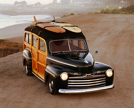 AUT 20 RK0015 04 © Kimball Stock 1946 Ford Woody Green With Surfboard Overhead 3/4 Front View At Beach