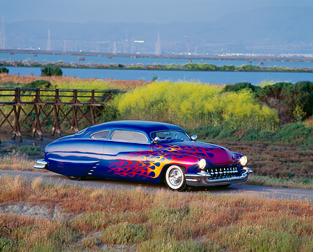 AUT 20 RK0060 02 © Kimball Stock 1949 Mercury Custom Street Rod Blue With Flames 3/4 Side View By Bushes At Dusk