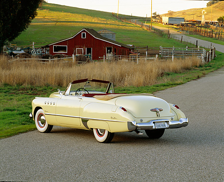 AUT 20 RK0089 01 © Kimball Stock 1949 Buick Roadmaster Yellow Convertible 3/4 Rear View On Pavement By Barn