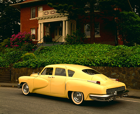 AUT 20 RK0101 02 © Kimball Stock 1948 Tucker Yellow 3/4 Rear View On Pavement By Green Plants And House