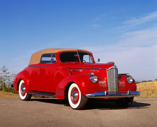 AUT 20 RK0118 02 © Kimball Stock 1941 Packard 160 Deluxe Convertible Red 3/4 Front View On Pavement