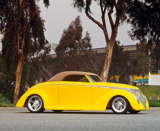 AUT 20 RK0132 07 © Kimball Stock 1940 Yellow Ford Custom Coupe 3/4 Front View On Pavement By Trees