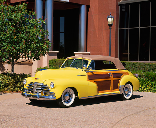 AUT 20 RK0142 01 © Kimball Stock 1948 Chevrolet Country Club Convertible Low 3/4 Side View On Pavement By Building And Trees