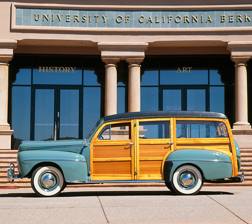 AUT 20 RK0148 05 © Kimball Stock 1948 Ford Woody Green Side View On Pavement By Building