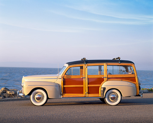 AUT 20 RK0161 01 © Kimball Stock 1946 Ford Super Deluxe Woodie Wagon Tan Side View On Pavement By Water Blue Sky