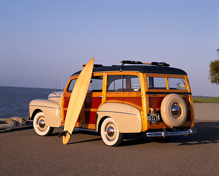 AUT 20 RK0165 01 © Kimball Stock 1946 Ford Super Deluxe Woody Wagon 3/4 Rear View On Pavement With Surfboard By Water