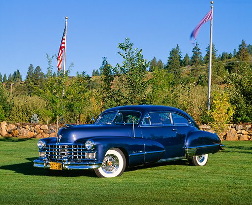 AUT 20 RK0179 01 © Kimball Stock 1947 Cadillac Sedanette Series 62 Blue 3/4 Front View On Grass By American Flags