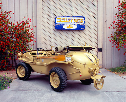 AUT 20 RK0226 02 © Kimball Stock 1943 VW Schwimmwagen 3/4 Rear View On Pavement By Red Flower Bush