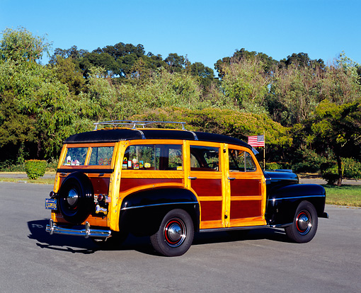 AUT 20 RK0247 01 © Kimball Stock 1948 Ford Woody Station Wagon Black 3/4 Rear View On Pavement By Trees Background