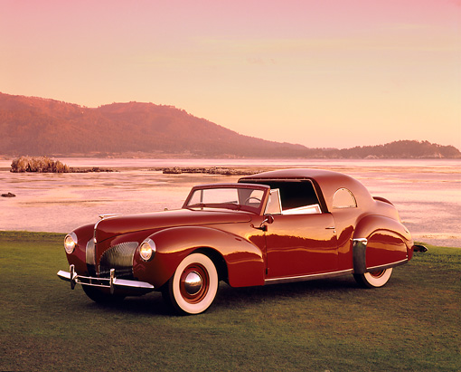 AUT 20 RK0253 03 © Kimball Stock 1940 Lincoln Continental Convertible Coupe Red 3/4 Side View On Grass By Water