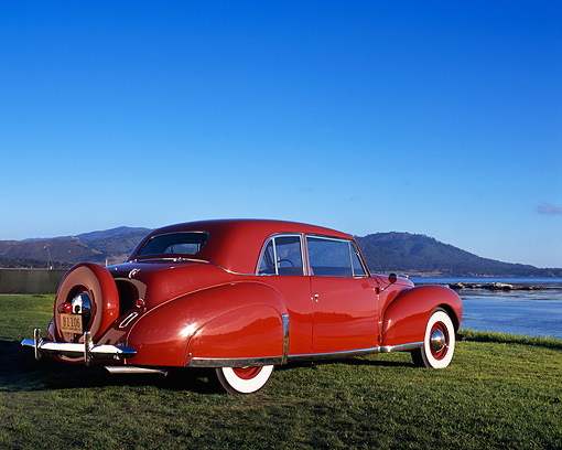 AUT 20 RK0261 02 © Kimball Stock 1941 Lincoln Continental Coupe Red Low 3/4 Rear View On Grass By Water Blue Sky
