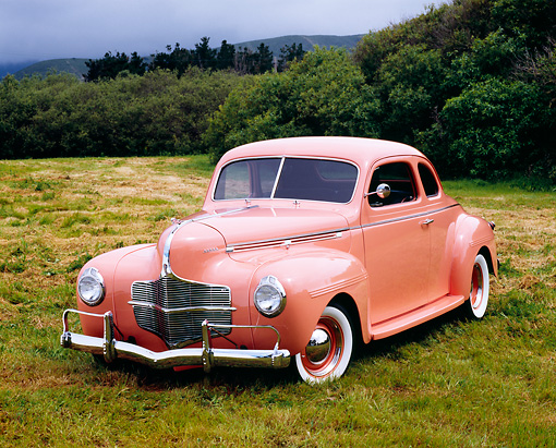 AUT 20 RK0269 03 © Kimball Stock 1940 Dodge Business Coupe Peach 3/4 Front View On Grass Bushes Background