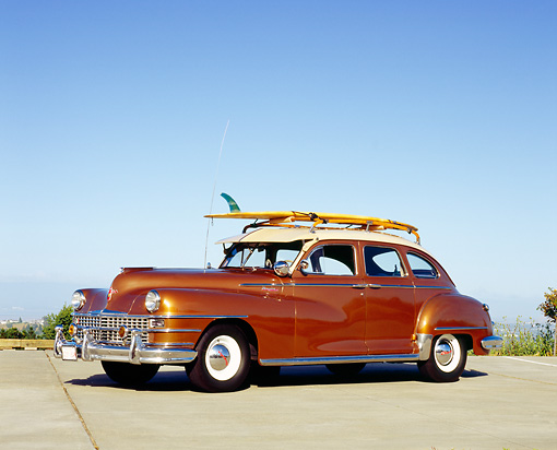AUT 20 RK0272 06 © Kimball Stock 1948 Chrysler Traveler Brown And Tan 3/4 Side View On Pavement With Surfboard