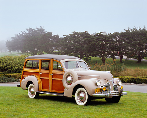 AUT 20 RK0278 02 © Kimball Stock 1940 Pontiac Six Hercules Station Wagon Woodie Tan 3/4 Front View On Grass By Trees