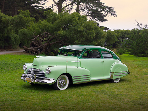 AUT 20 RK0316 01 © Kimball Stock 1948 Chevrolet Fleetline Two Tone Green 3/4 Front View On Grass Trees Background