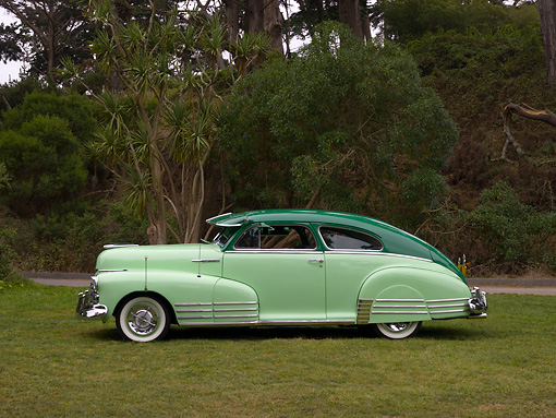 AUT 20 RK0317 01 © Kimball Stock 1948 Chevrolet Fleetline Two Tone Green Profile View On Grass Trees Background