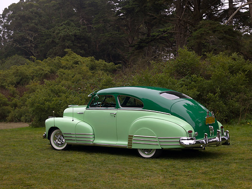 AUT 20 RK0321 01 © Kimball Stock 1948 Chevrolet Fleetline Two Tone Green 3/4 Rear View On Grass Trees Background