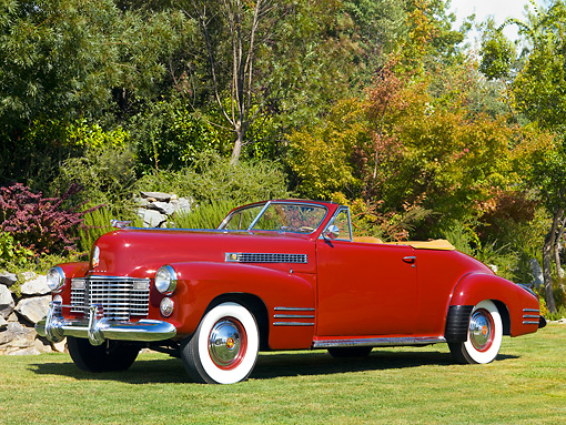 AUT 20 RK0322 01 © Kimball Stock 1941 Cadillac Deluxe Convertible Coupe Oxblood Red Front 3/4 View On Grass By Trees