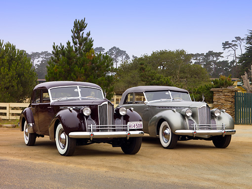 AUT 20 RK0325 01 © Kimball Stock 1940 Packard Darrin Sedan Convertible Silver And Sport Sedan Burgundy Front 3/4 View On Dirt