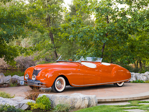 AUT 20 RK0362 01 © Kimball Stock 1941 Chrysler Newport Dual Cowl Phaeton Red 3/4 Front View On Platform By Trees