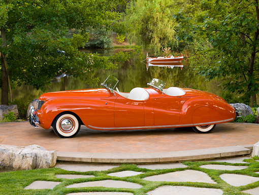AUT 20 RK0363 01 © Kimball Stock 1941 Chrysler Newport Dual Cowl Phaeton Red 3/4 Front View On Platform By Lake And Trees