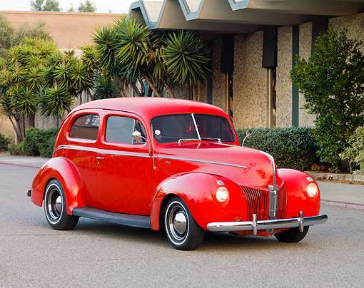 AUT 20 RK0368 01 © Kimball Stock 1940 Ford 2-Door Sedan Red 3/4 Front View On Pavement By Building And Trees