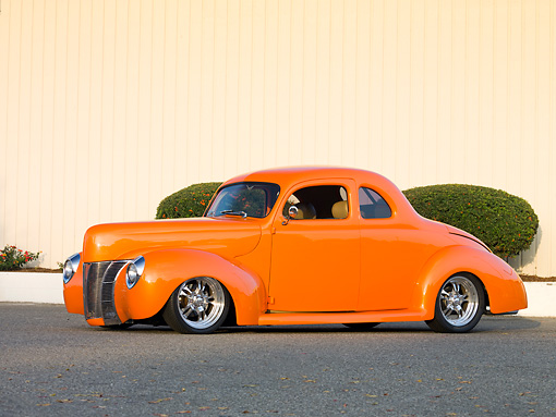 AUT 20 RK0372 01 © Kimball Stock 1940 Ford Deluxe Coupe Orange 3/4 Front View On Pavement By Fence