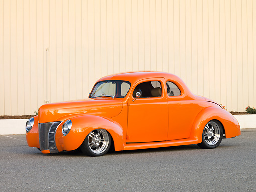 AUT 20 RK0373 01 © Kimball Stock 1940 Ford Deluxe Coupe Orange 3/4 Front View On Pavement By Fence