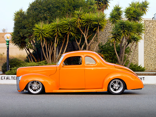 AUT 20 RK0374 01 © Kimball Stock 1940 Ford Deluxe Coupe Orange Profile View On Pavement By Trees