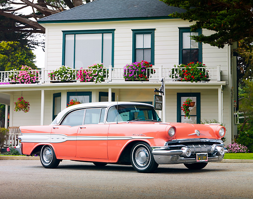 AUT 21 BK0019 01 © Kimball Stock 1957 Pontiac Chieftain Coral And White 3/4 Front View On Pavement By House