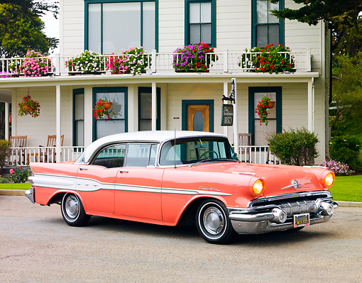 AUT 21 BK0020 01 © Kimball Stock 1957 Pontiac Chieftain Coral And White 3/4 Front View On Pavement By House