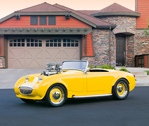 AUT 21 BK0023 01 © Kimball Stock 1958 Austin-Healey Sprite (AKA Bugeye) Convertible Hot Rod Yellow 3/4 Front View On Pavement By House