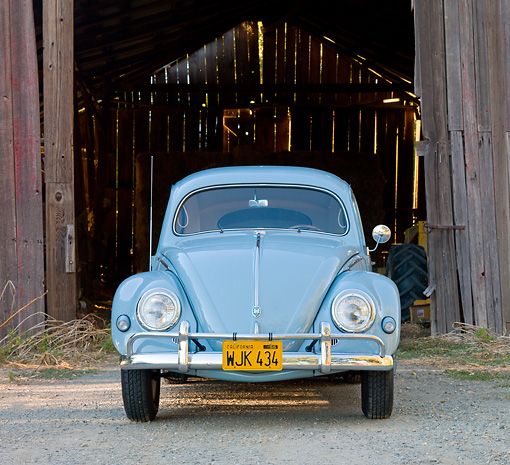 AUT 21 BK0029 01 © Kimball Stock 1957 Volkswagen Beetle Light Blue Head On View On Gravel By Barn
