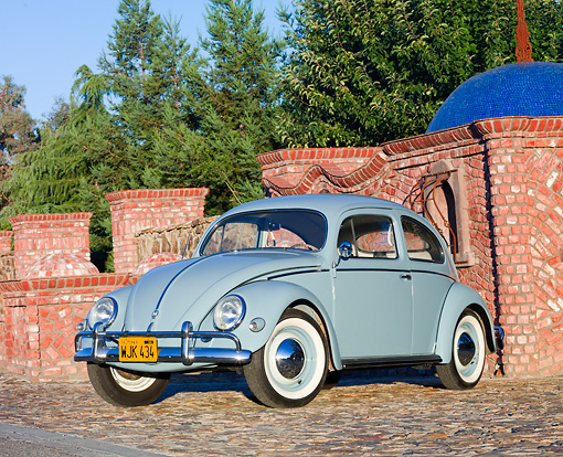 AUT 21 BK0031 01 © Kimball Stock 1957 Volkswagen Beetle Light Blue 3/4 Front View On Cobblestone By Brick Wall