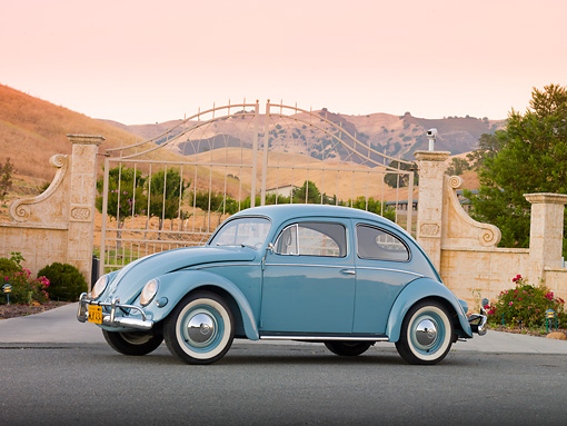 AUT 21 BK0033 01 © Kimball Stock 1957 Volkswagen Beetle Light Blue 3/4 Side View On Pavement By Gate And Hills