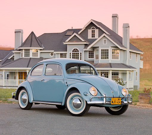 AUT 21 BK0034 01 © Kimball Stock 1957 Volkswagen Beetle Light Blue 3/4 Front View On Pavement By House At Dusk
