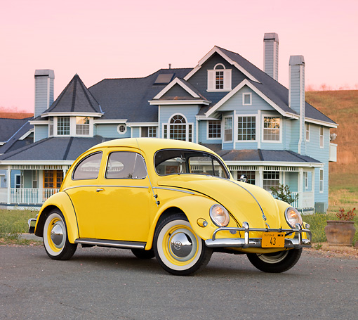 AUT 21 BK0035 01 © Kimball Stock 1957 Volkswagen Beetle Yellow 3/4 Front View On Pavement By House At Dusk
