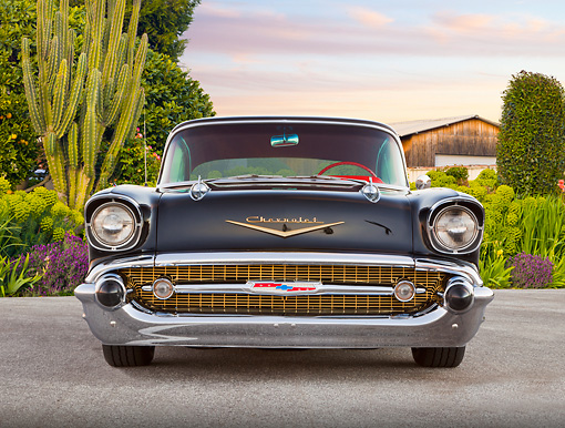 AUT 21 BK0039 01 © Kimball Stock 1957 Chevrolet Bel Air Black Front View On Pavement By Cactus, Shrubs And Barn