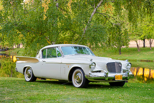 AUT 21 BK0136 01 © Kimball Stock 1957 Studebaker Golden Hawk White And Gold 3/4 Front View On Grass By Water And Trees
