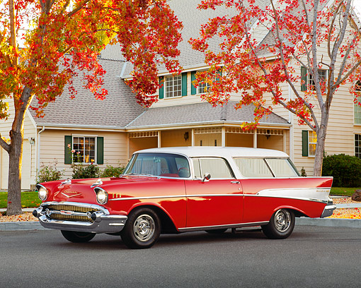 AUT 21 RK0046 10 © Kimball Stock 1957 Chevy Nomad Wagon Red And White 3/4 Front View On Pavement By House And Autumn Trees