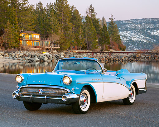 AUT 21 RK0089 01 © Kimball Stock 1957 Buick Special Convertible Blue & White 3/4 Front View On Pavement By Lake And Cabin