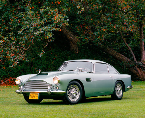 AUT 21 RK0092 09 © Kimball Stock 1959 Aston Martin DB4 Series One Light Green 3/4 Front View On Grass By Trees