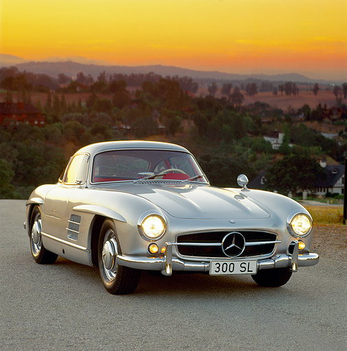 AUT 21 RK0105 04 © Kimball Stock 1956 Mercedes 300SL Gullwing Silver 3/4 Front On Pavement Headlights On Sunset
